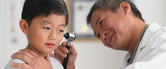 Asian doctor examining a child's ears