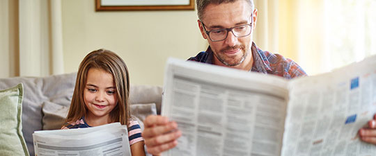 Father and daughter reading newspaper