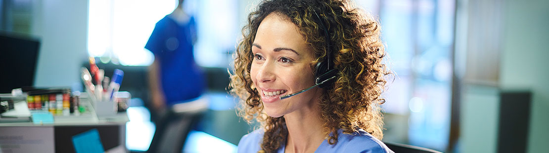 Female nurse on phone headset in front of computer